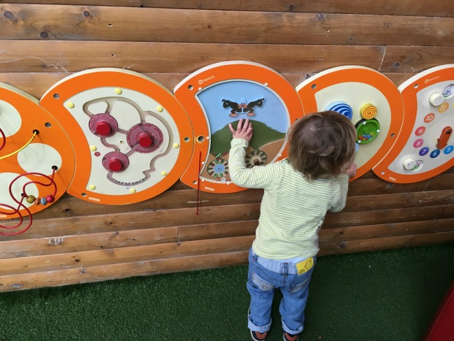 toddler-at-Parc-play-cardiff-playing-with-a-wall-mounted-toy-that-spins