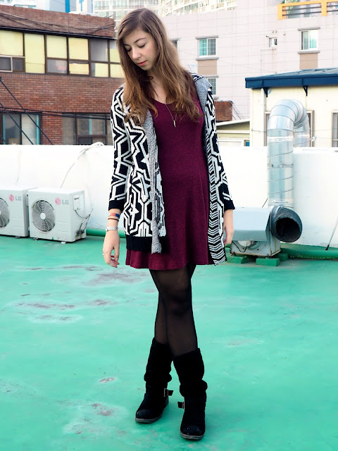 Winter Prints | outfit of black and white bold patterned cardigan over a short purple knitted dress, with black tights and tall suede boots
