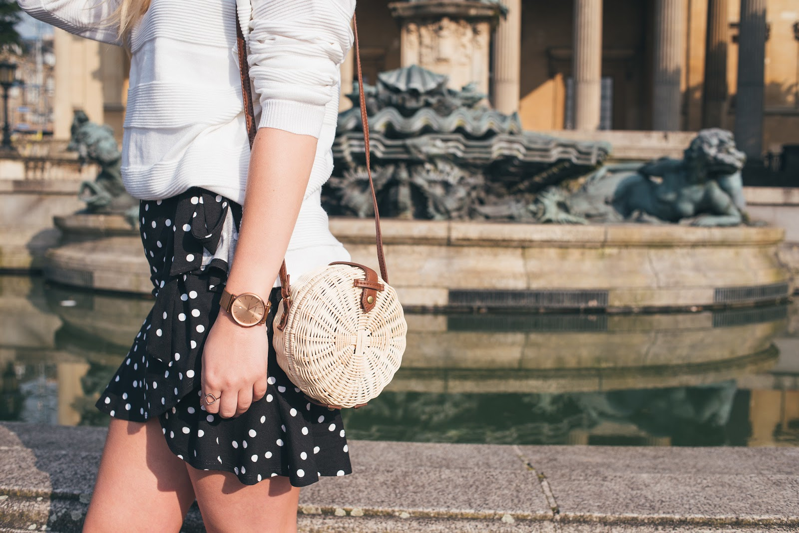 Close up of Polka Dot Skirt with ASOS Straw Round Bag in front of Victoria rooms fountain