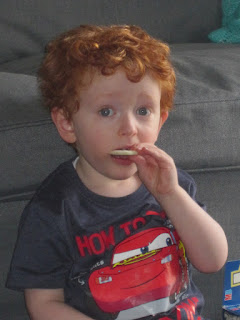 Red haired toddler eating a wafer snack