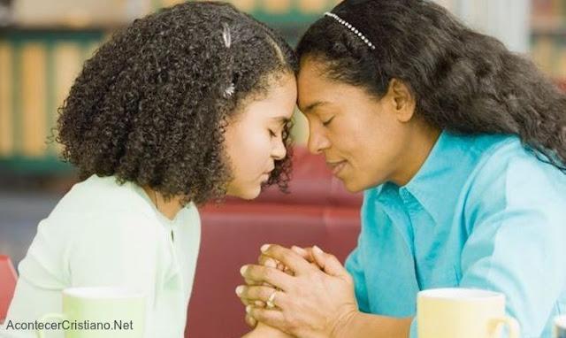 Madre orando con su hija