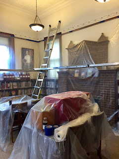 Library Closed Until 5:30 Today, April 5th || photo of shelves, tables, etc. coverd in plastic with scaffolding set up