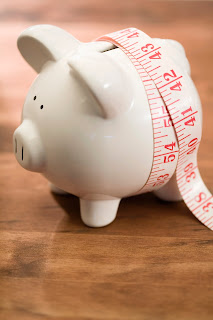 Image of Piggy Bank with a tape measure wrapped around it.