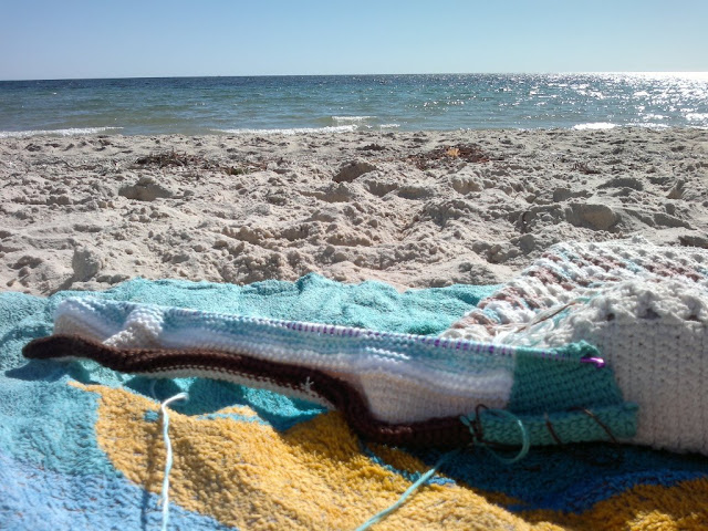 A closer view of the previous photograph: crochet in progress on a long double-ended tricot hook is laid out on a beach towel next to a crocheted bag. The scene is a sandy beach looking across the water which has no surf, just gentle foam lapping at the shoreline.