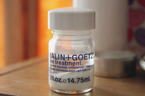 malin + goetz acne treatment sitting on a wooden dressing table; the formula has separated, so a white powder sits on the bottom, and a clear liquid sits on top.