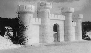 A black and white photograph showing the front wall of a castle, built from snow.