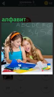 две ученицы за столом и написан алфавит на доске