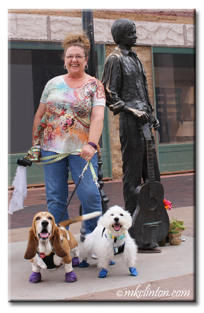 Basset Hound, Westie & M. K. Clinton standing on a corner in Winslow, Arizona