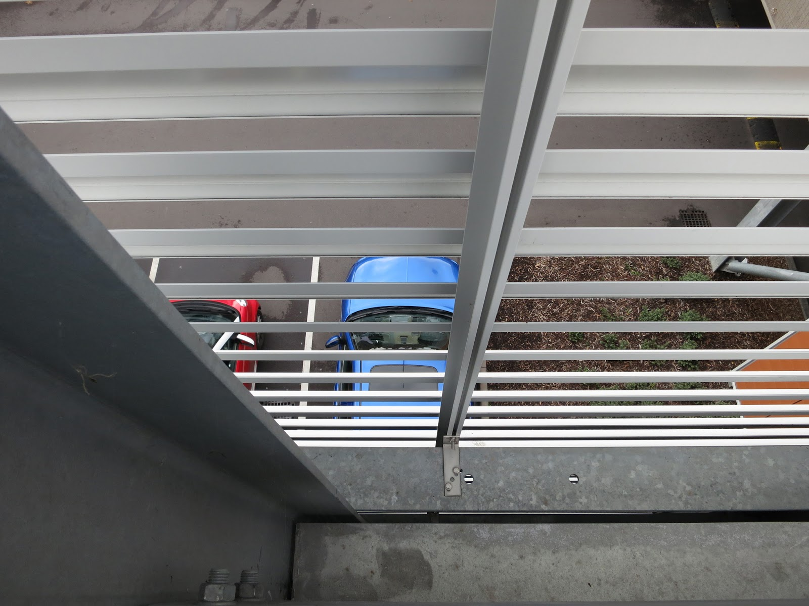 Blue and red cars seen through railing in multi-storey carpark
