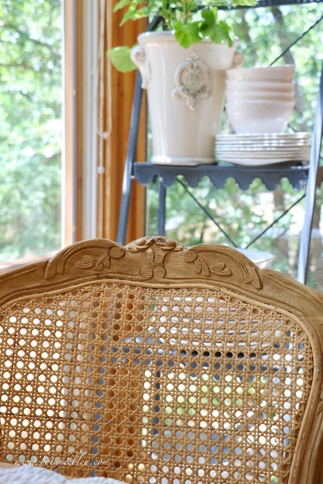 French Country cane back dining chair with curved carved wooden frame