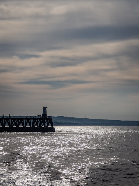 Photo of the sun reflecting on the water by Maryport pier