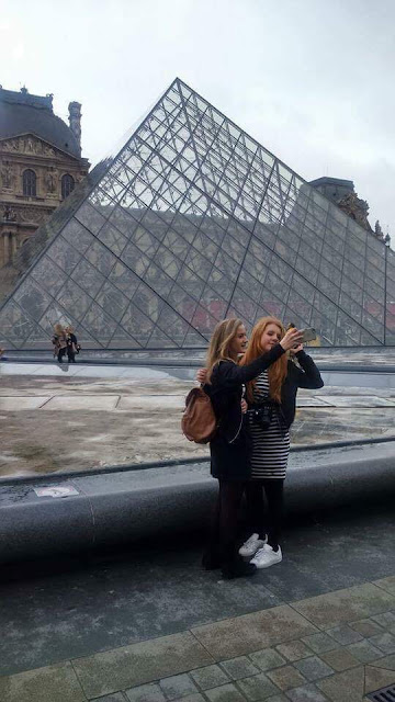 Me and my friend taking selfies in front of the glass pyramid at the Louvre, Paris