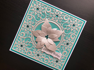Hand made Christmas card with a die cut poinsettia and die cut snowflake background panel.