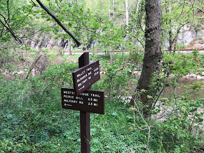 Photo of a sign in a lot of greenery. The Valley Trail points one direction, the Western Ridge Trail another.