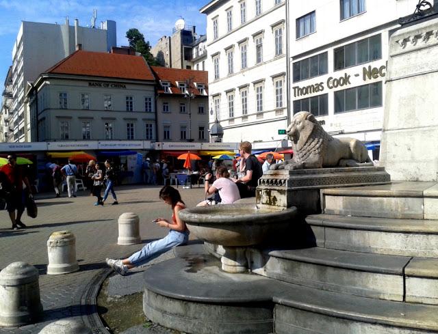 Budapest, Vörösmarty tér, 89. Ünnepi Könyvhét, 2018. június 9., Oroszlános kút és olvasó emberek, hátérben könyves standok és napernyők.