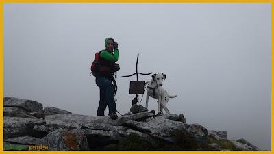 Vistas a la cruz de cumbre en las Peñas de Faro bajo la niebla