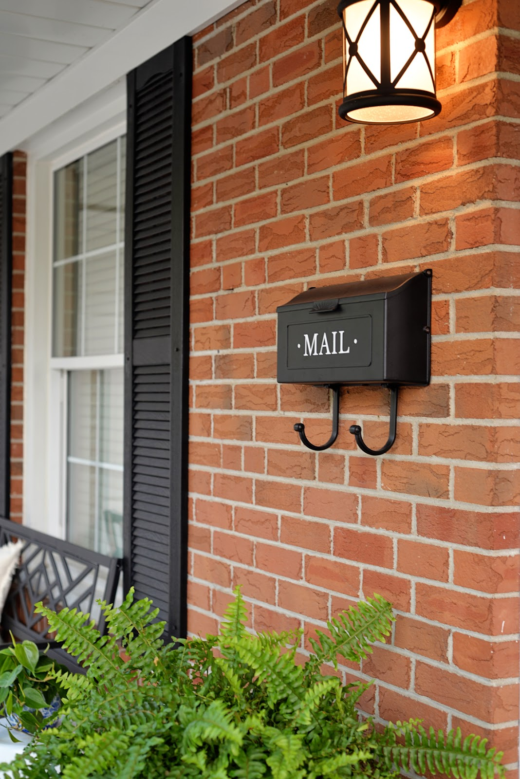front porch decorating ideas for summer, red brick house with black shutters and mailbox decal