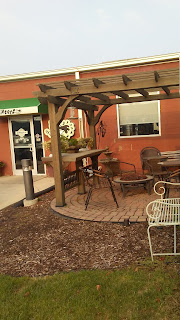 patio with artistically mismatched benches and pergola behind Jitters Donuts in downtown Sioux City, Iowa