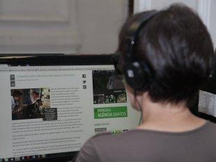 Prefeitura de Santos: mulher, de costas, olha pra tela de computador que tem imagem com descrição em evidência #PraCegoVer