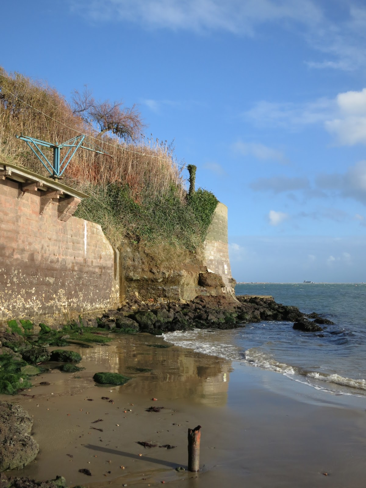 Tall wall to stop sea eroding cliff.