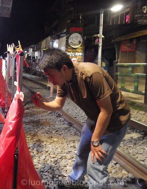 writing wishes on a folded skylantern at the railroad tracks of Shifen Old Street