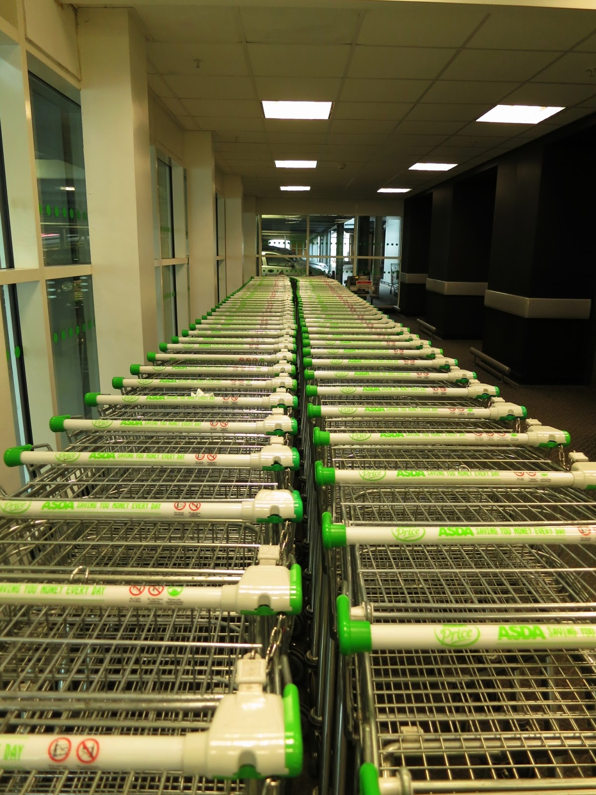 Two long lines of trolleys in supermarket foyer