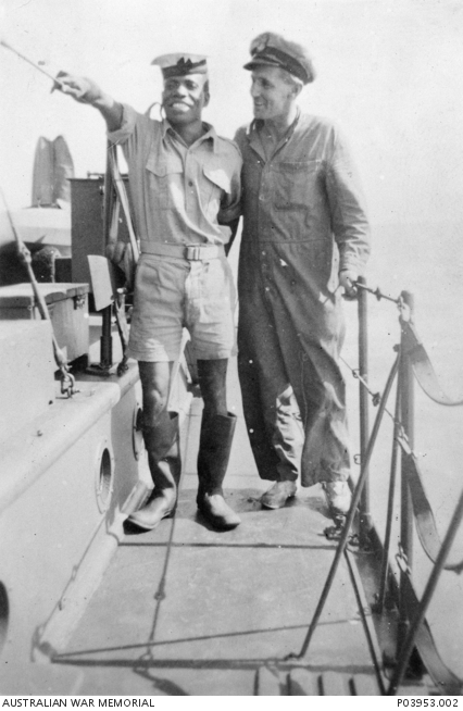 Informal portrait of Officer Cook Namma Will Will from Mussau Island and Engineer Petty Officer R Swan (possibly S/4450 Roy Allen Swan) on board Motor Launch (ML) 1321, used by Z Special Unit.