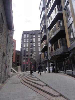 Lite torg med en bred trapp mellom noen mer moderne bygninger.