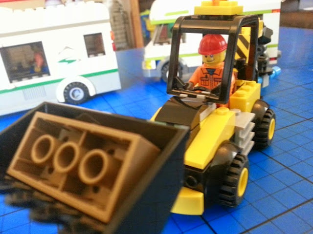 Yellow LEGO Juniors digger with brown brick in scoop