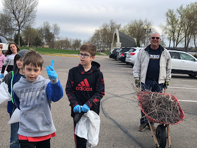5 kids wearing gloves and carrying plastic bags and one adult with a wheelbarrow filled with brush walk in a parking lot