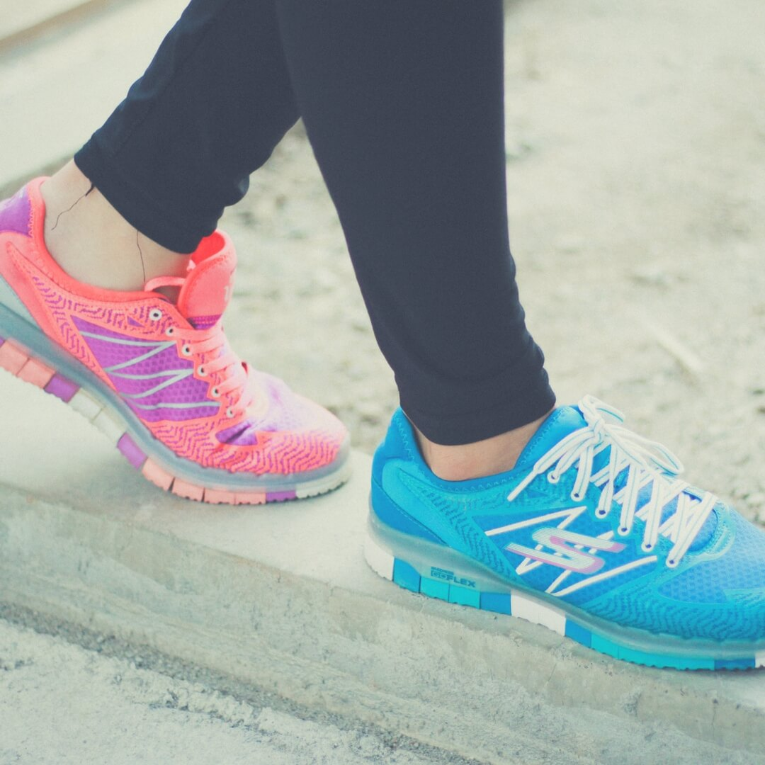 "A person wearing a pair of trainers, only the legs and trainers are pictured. The person is wearing one bright blue trainer and one bright pink trainer, with black skin-tight leggings. The person is standing on a pavement edge, walking with the pink trainer behind the blue one. Image for ""Post Comment Love 16th - 18th March""."