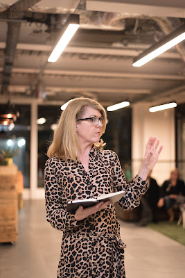 Steph wearing glasses and holding a notebook looking to her left as she speaks to an audience