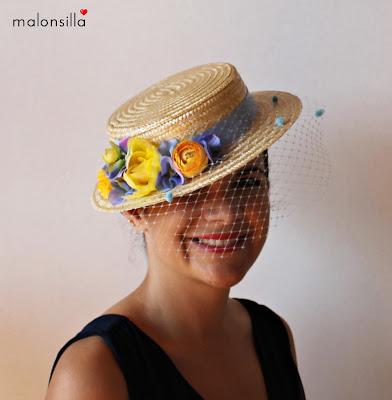 Imagen que muestra el canotier, sombrero de copa baja, modelo Argentina con tapafeas de plumeti y flores en amarillo y azul claro.