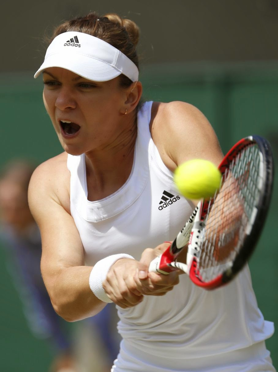 Simona Halep of Romania plays a return to Zarina Diyas of Kazakhstan during their women's singles match at the All England Lawn Tennis Championships in Wimbledon, London, Tuesday, July 1, 2014.