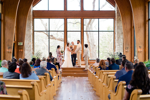 """Summer and David decided on a small, intimate wedding, tying-the-knot at the tucked-away and woodsy Thunderbird Chapel in Norman, OK.  Little did Summer know when David became her personal trainer, that they would one day be married.  This was a second marriage for both, and Summer's bridesmaid and maid of honor, and David's best man were their respective children.    Summer was stunning in her trumpet style lace wedding dress, """"killer"""" glittery heels, holding a beautiful, handmade bouquet consisting of pink roses, white lilies, pink freesia, white baby's breath and greenery.  And David looked dashing in his champagne-colored, three-piece suit, light blue tie, and a single rose boutonniere. Such a beautiful couple on their wedding day!        Summer's dad was brought to tears during his """"First Look;"""" it was clear that this was a special day for him as well.  The littlest girls led the way down the aisle, dropping rose petals, and racing each other to the end, while David and his son watched with awe as Summer, his soon-to-be-bride, walked down the aisle, arm-in-arm with her dad.  The ceremony included the assembly of a Unity Cross, signifying the two becoming one together with their faith in Christ, and hand-written vows.  At the end of the ceremony, David, caught up in the emotion of the """"I do's,"""" kicked up his heel in celebration!     After the ceremony, the bride and groom were greeted by a throng of well- wishing guests blowing bubbles.  The day was filled with heartfelt moments shared by the people they loved, and we tried our best to capture every beautiful detail, big and small."""