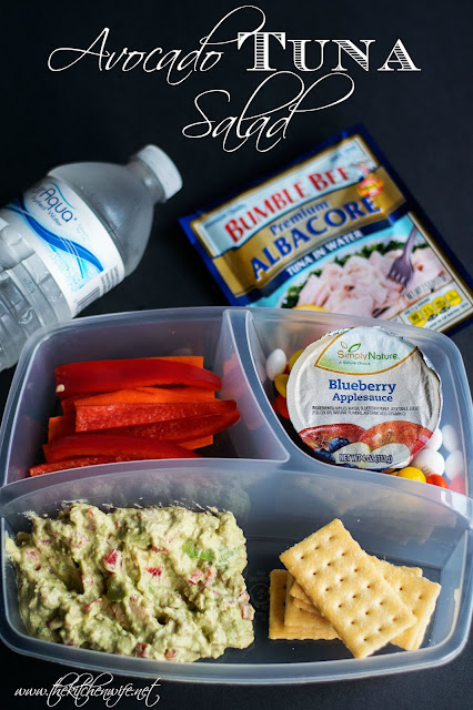 A picture of a child's lunch container with the tuna salad, carrot sticks, apple sauce and crackers.