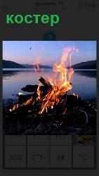 На берегу в сумерках горит костер потрескивая дровами и виден из далека