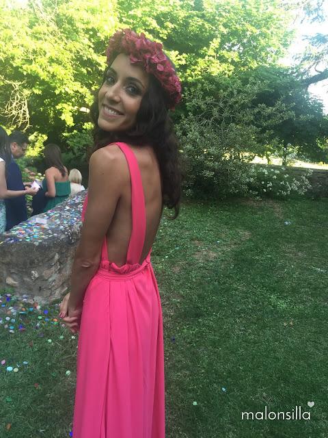 Invitada boda con escote en la espalda, vestido largo rosa y corona de flores preservadas color buganvilla