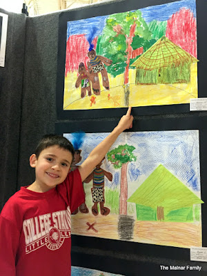 Jackson smiling and pointing to his artwork at the Art Show.