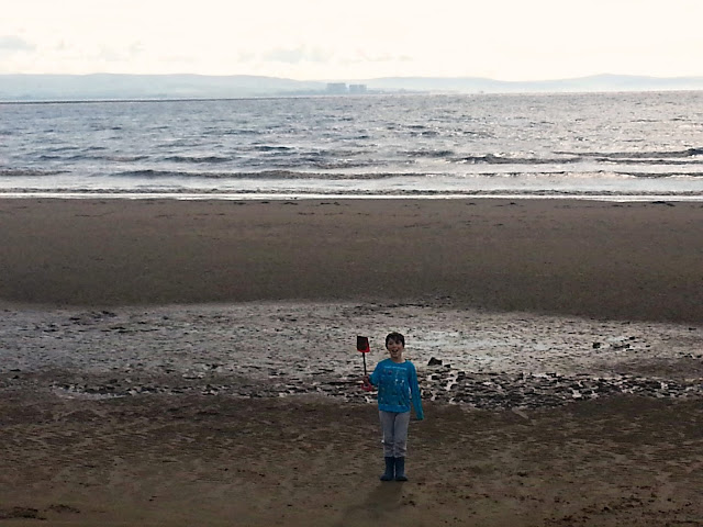 Boy on beach from a distance, holding spade.