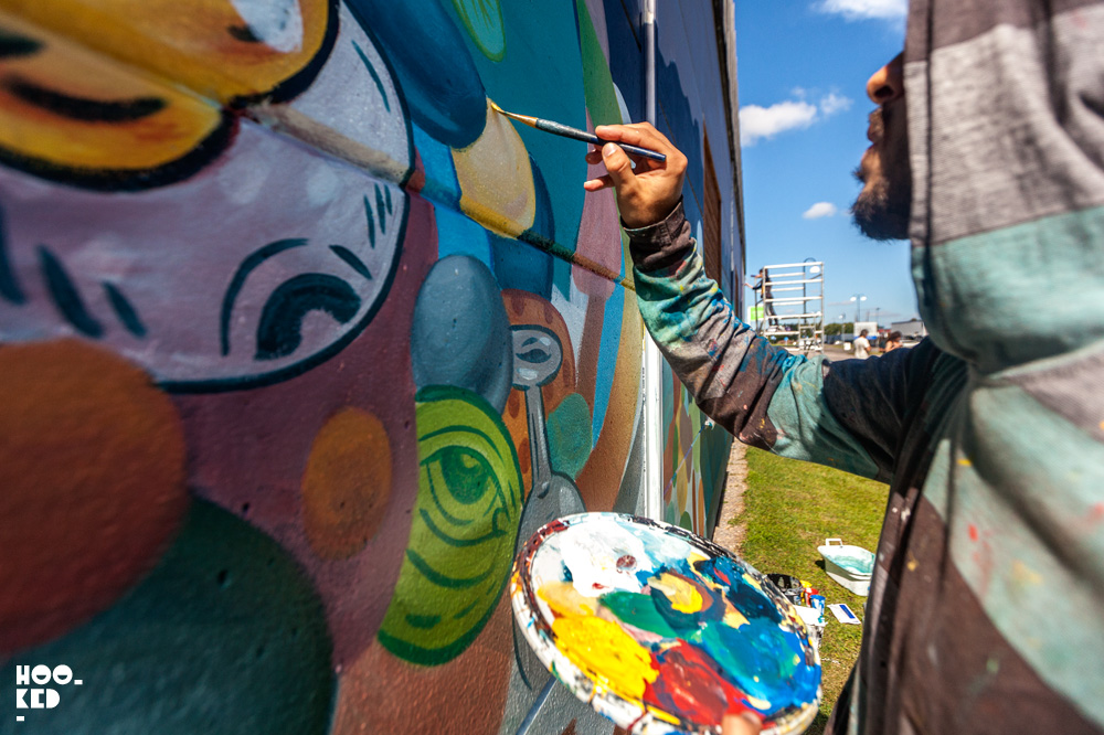 Mexican street artist Mario Maple at work painting a mural in Street Art Mural in Falköping, Sweden