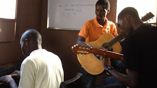 michael phils and pastor john olatunji playing the guitar