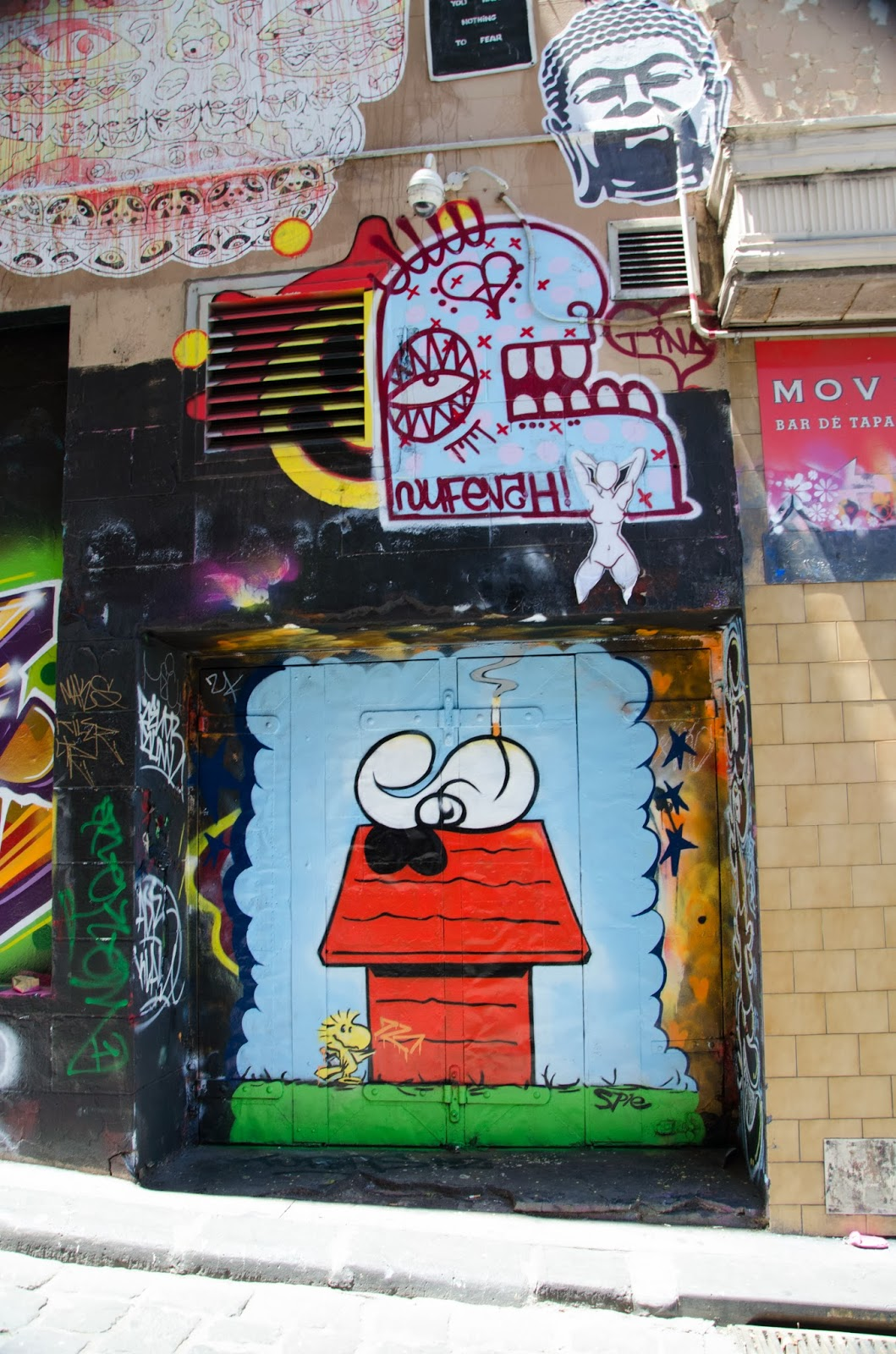 a grafitti of a smoking snoopy on a black door of a building in melbourne