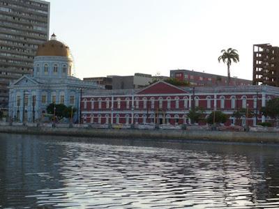 Fotografia colorida dos edifícios onde funcionam a Assembleia Legislativa e o Ginásio Pernambucano, na rua da Aurora, às margens do rio Capibaribe.