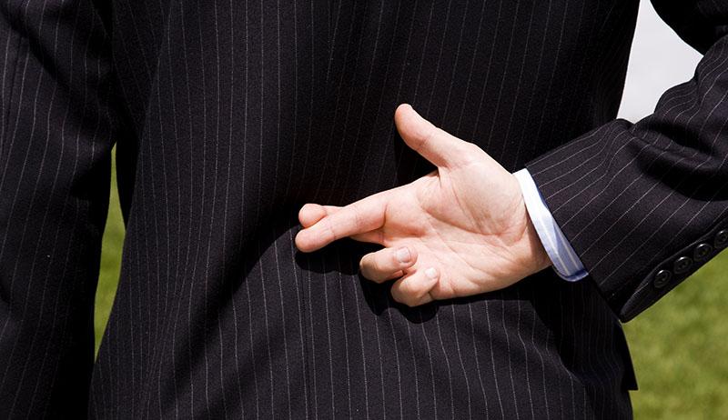 Человек в костюме скрестил пальцы за спиной