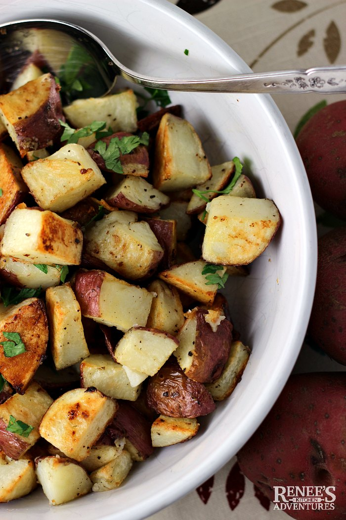 Garlic Roasted Potatoes in serving bowl with spoon