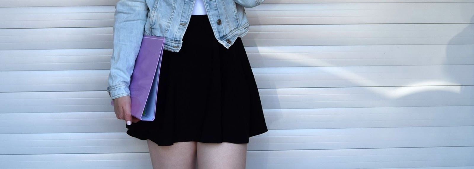 Lower body shot showing the black skater skirt, white top and blue light washed denim jacket. The model is also wearing a white nail polish and is carrying a pastel purple binder