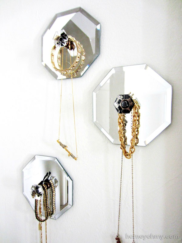 Combine dollar store mirrors and cute knobs to make decorative jewelry hangers.