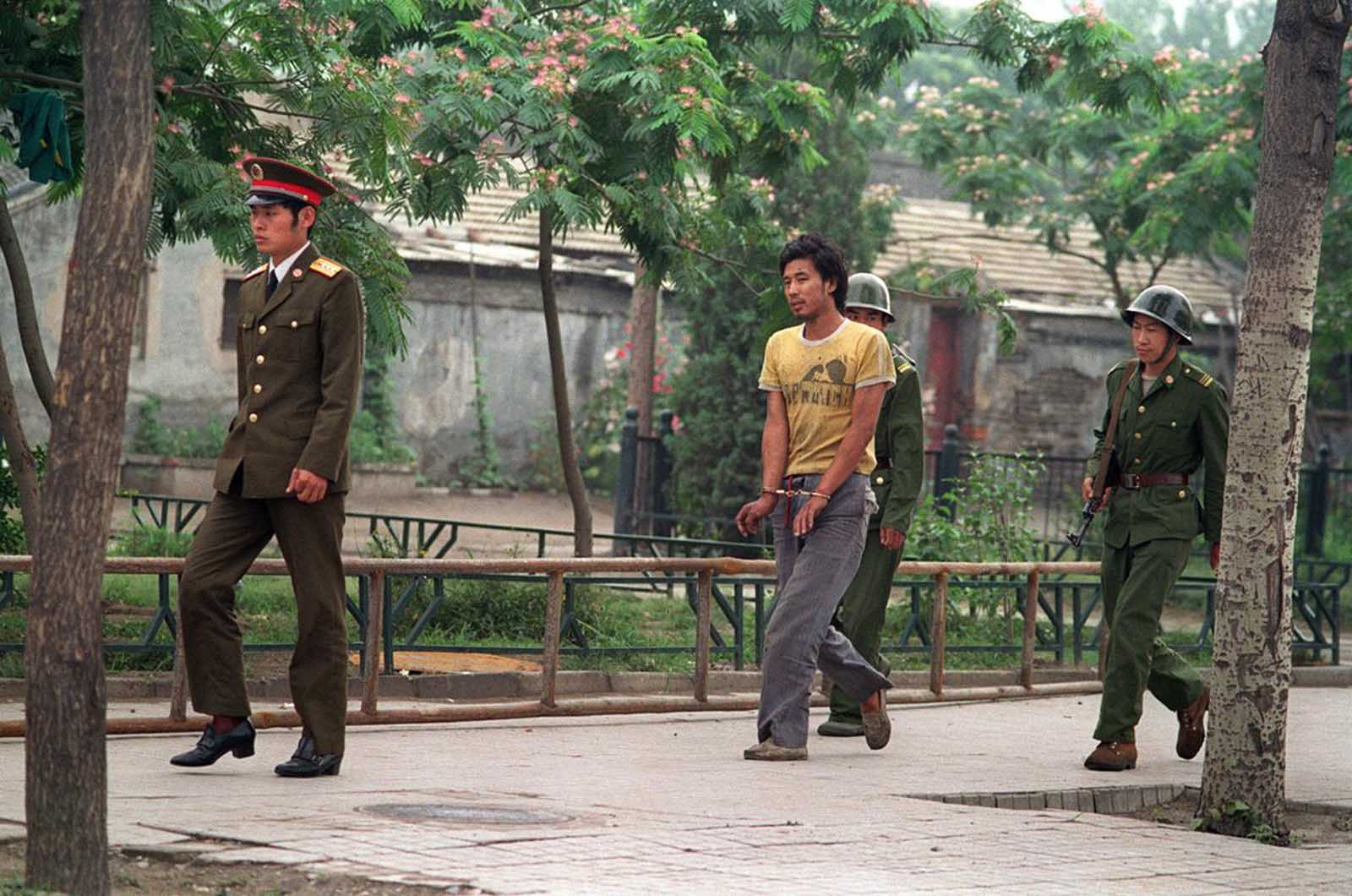 A handcuffed man is led by Chinese soldiers on a street in Beijing, in June of 1989, as police and soldiers searched for people involved in the April-June pro-democracy protests.
