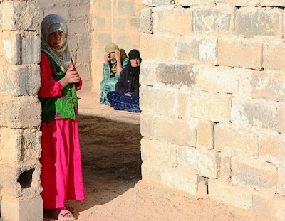 TYpical cement block wall, an Iraqi girl stands shyly in the shadow as we look in towards the inner courtyard